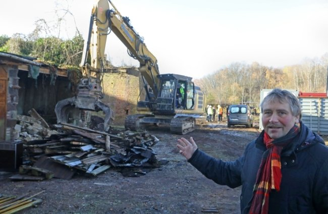 Ortschef Erik Seidel zeigt auf den alten Schuppen. Der fällt nun genauso dem Bagger zum Opfer wie im Hintergrund die Stütze der alten Seilbahn.