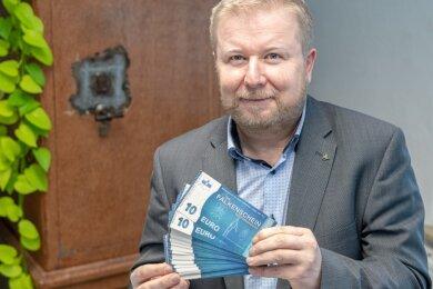 """Falkensteins Bürgermeister Marco Siegemund (CDU) präsentiert ein Bündel """"Falkenscheine"""": Die Idee der bezuschussten Bons hat man sich von der Partnerstadt Stein abgeschaut."""