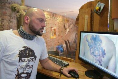 Nico Roth zeigt auf dem Monitor  eines seiner vielen Tattoos, die er in seinem Geschäft verarbeitet hat.