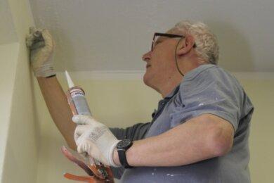 Peter Lüpke von den Mittweidaer Malerwerkstätten erledigt noch kleine Restarbeiten im Treppenhaus.