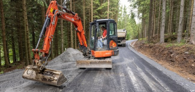 Ein Abschnitt des Bärenfangwegs nahe Oberwiesenthal hat in den vergangenen Tagen eine neue Asphaltdecke erhalten. Das Foto zeigt Steffen Schreier bei Anpassungsarbeiten zur Anbindung eines anderen Waldwegs.
