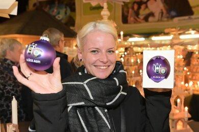 Besucherin Romy Lorenz aus Oelsnitz hält die neue FCE-Weihnachtskugel in Händen.
