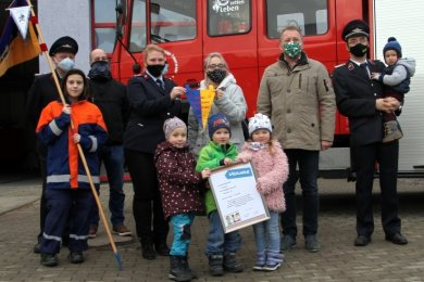 Bürgermeister Ronny Hofmann (2.v.r.) übergibt die Gründungsurkunde an die Kinderjugendwarte Marika Uhlemann und Julia Bludau (3.v.r.) im Beisein des Wehrleiters (r.), des Jugendwarts (l.) sowie von Kindern.