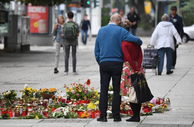 Passanten stehen am Tatort an der Brückenstraße, an dem zahlreiche Blumen und Kerzen niedergelegt wurden.