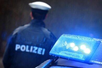 Ein Polizist steht vor einem Streifenwagen.