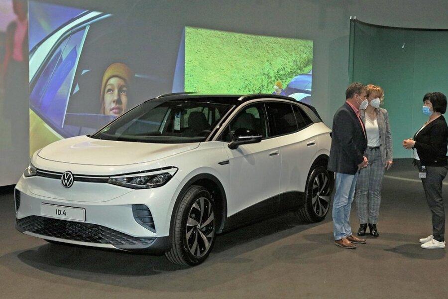 Jacqueline Heyer-Mertens (M.) und ihr Mann Mario Heyer aus Suhl haben am Freitag als erste Kunden ihren VW ID.4 in der Gläsernen Manufaktur in Dresden abgeholt. Gebaut wird der neue vollelektrische Sportgeländewagen derzeit in Zwickau sowie in zwei Werken in China.