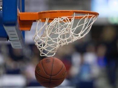 Ein Basketball fällt durch das Netz vom Basketballkorb.