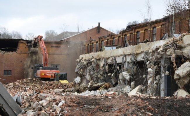 Der Abrissbagger frisst sich derzeit im hinteren Teil des alten Betriebsgeländes durch die Gebäude. Im Uhrzeigersinn geht es voran, sodass der Bereich am Bahnhof zuletzt abgerissen wird.