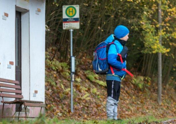 Ein Grundschüler wartet an einer Bushaltestelle.