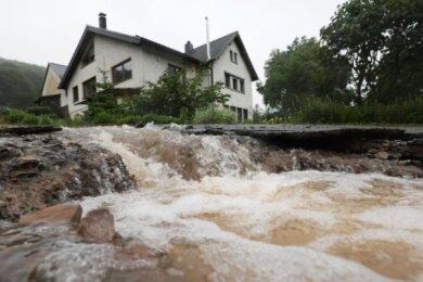 Wasser läuft bei Heimbach an einem Haus vorbei den Hang hinunter