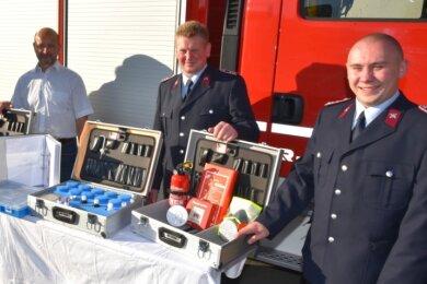 Fünf Koffer haben Gemeindewehrleiter Rico Steudel (l.), Jugendwart Mario Nävie (zweiter von rechts) und Vize-Jugendwart Tobias Nävie (rechts) von Bürgermeister Berthold Valentin (zweiter von links) erhalten.