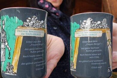 """Die Christmarkt-Tasse 2020 ist in der Tourist-Information erhältlich. Die neunte Edition ziert ein Motiv des Bergmaurers sowie ein Spruch zum Welterbe """"Montanregion Erzgebirge/Krušnohorí""""."""