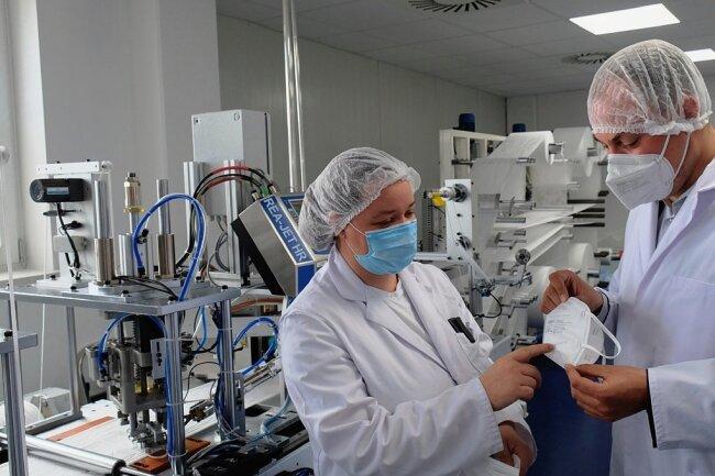 """Endlich läuft die Produktion. TEG-Chef Timo Fischer mit Mitarbeiterin Nadin Pretzlaff in der neuen FFP2-Maskenfertigung - wöchentlich 100.000 Stück laufen vom Band. In Vorbereitung ist bereits die Produktion antiviraler Masken vom Typ FFP2 NR """"Viruskiller"""", in vier Wochen könnte es losgehen."""