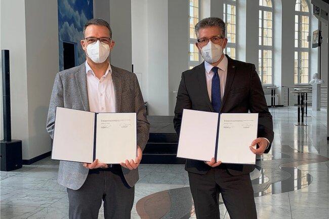 Der Generalintendant der Theater Chemnitz, Dr. Christoph Dittrich (l.), hat seinen Vertrag in der Stadt verlängert. In Anwesenheit von Bürgermeister Ralph Burghart (r.) unterzeichnete er seine neue Vereinbarung, die bis 2028 Gültigkeit hat.