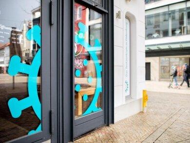 Ein überdimensionales Coronavirus klebt am Fenster eines Cafés in der Oldenburger Innenstadt, das derzeit als Testzentrum genutzt wird.