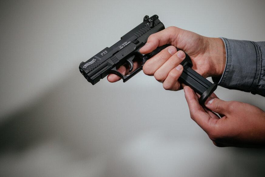 Ein Mann lädt eine Schreckschuss-Pistole Walther P22 mit einem Magazin.