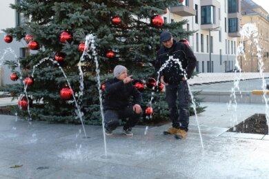 Lukas Neubert und Marko Korn (r.) von der Firma Aquaprojekt Plauen beim Testlauf des Wasserspiels auf dem Solbrigplatz.