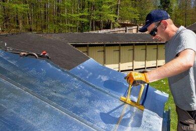 Die Dächer der sanierten Kabinen im Freibad Haselbrunn werden derzeit mit Zinkblech belegt.