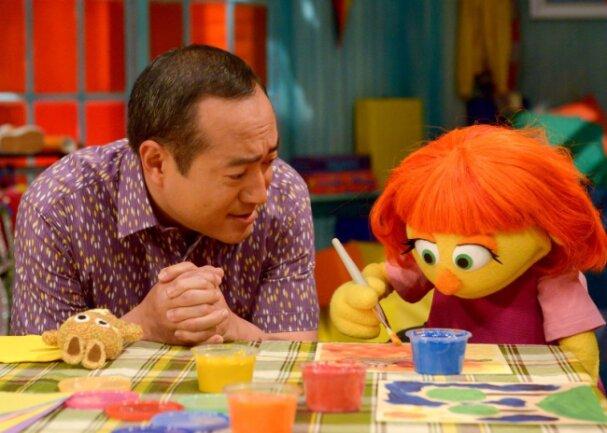 """""""Julia"""" (rechts), eine talentierte Sängerin, hat orangene Haare, einen Kuschelhasen und Autismus. Sie ist der neue Star der """"Sesamstraße""""."""
