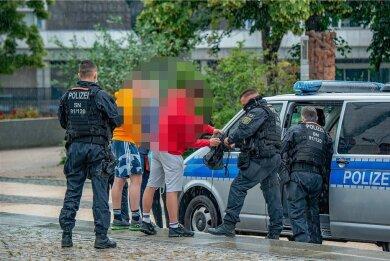 Polizeibeamte kontrollieren eine Gruppe von Jugendlichen im Stadthallenpark. Mit derlei verdachtsunabhängigen Durchsuchungen soll Drogen- und Gewaltkriminalität bekämpft werden.
