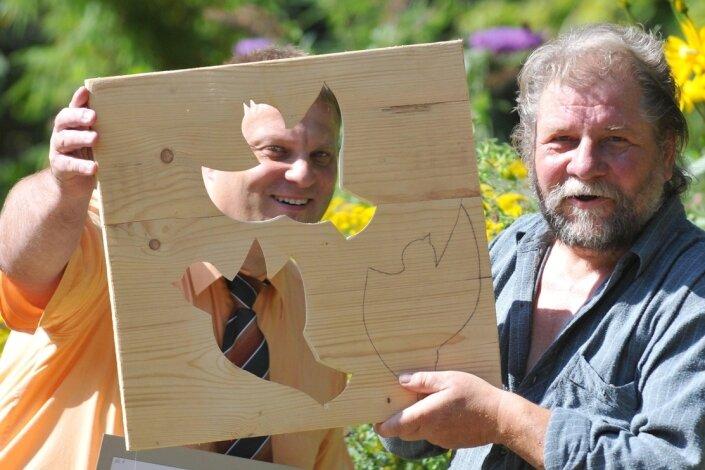 Bürgermeister Martin Antonow (links) und Holzgestalter Volker Beyer mit den Entwürfen für die neu gestaltete Eingangstür zum Langenauer Kindergarten.