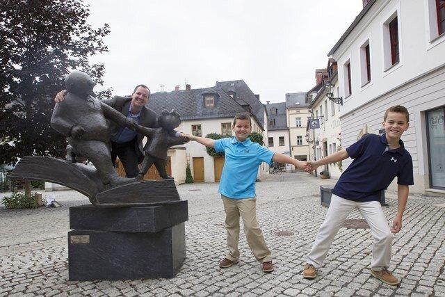 Peter Ohser, Enkel von Erich Ohser mit seinen Söhnen v.re.: Owen und Graham an der Vater-und-Sohn Skulptur vor der e.o.plauen Galerie an der Nobelstr.