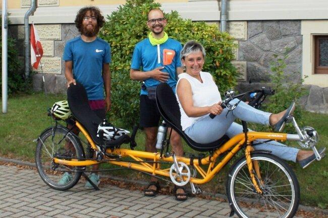 Tilman Jiménez Reichow (l.) und Malte Boßert bei ihrem Zwischenstopp in Neukirchen. Bürgermeisterin Ines Liebald macht auch auf dem Liegerad-Tandem eine gute Figur.
