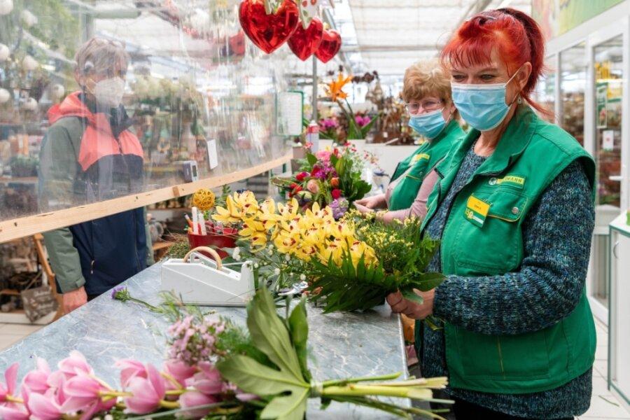In der Gartenabteilung des Leitermann-Baumarktes in Rochlitz haben Elke Schmidt (vorn) und Kerstin Hoyer am Freitag jede Menge Blumensträuße für den bevorstehenden Muttertag gebunden. Teile des Marktes sind aber weiter für Kunden wegen der Corona-Schutzregelungen abgesperrt.