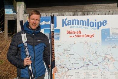 Tim Tröschel, vor einigen Jahren selbst erfolgreicher Langläufer, mit Skiern der Marken Aschberg und Klingenthal aus seiner Werkstatt vor der Karte der Kammloipe in Mühlleithen.