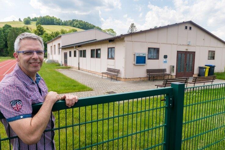 Jens Rößner, Vorsitzender des Blumenauer Ortschaftsrates, an der bereits sanierten Turnhalle, deren Sozialanbau (im Vordergrund) erneuert werden soll.