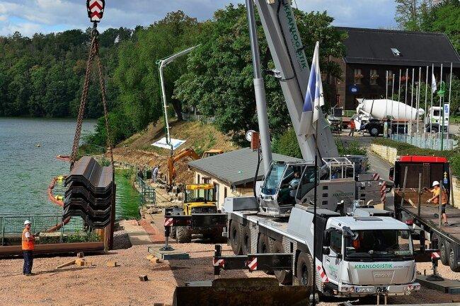 Per Kran sind die Stahlteile für die Spundwände auf die Baustelle gehoben worden, die voraussichtlich ab 7. September in den Boden vor der Ufermauer mit einer Ramme eingebaut werden.