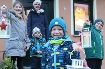 Diese drei Lichter gingen am Dienstag in Borstendorf auf die Reise: Stefanie Zickmantel und Luca schauen zu, wie Selia, Thore und Mats (v. l.) die Laternen halten.