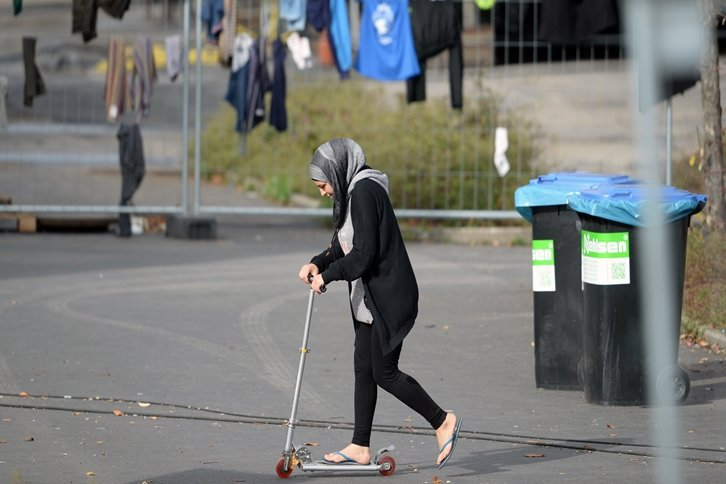 Eine Frau fährt mit einem Roller über den Hof ihrer Asyl-Unterkunft in Niederau (Sachsen).
