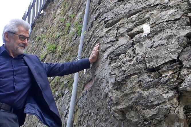 Bürgermeister Bernd Pohlers wirft einen Blick auf die Schäden an der Stützmauer am Torberg.
