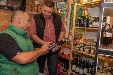 Sandro Schink (rechts) hat die Schanzenbaude Rodewisch um einen Laden erweitert. Dort werden neben anderen regionalen Produkten auch die Aronia-Erzeugnisse von Frank Sommer (links) angeboten.Foto: David Rötzschke