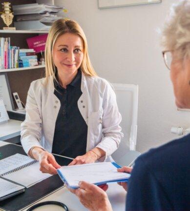 Hausärztin Dr. Raina Hübschmann (links) hat eine Corona-Schwerpunktpraxis in Zwönitz. Hier im Gespräch mit einer Mitarbeiterin.