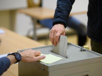 Ein Wähler wirft bei der Stimmabgabe zur Bundestagswahl im Wahllokal seinen Stimmzettel in eine Wahlurne.