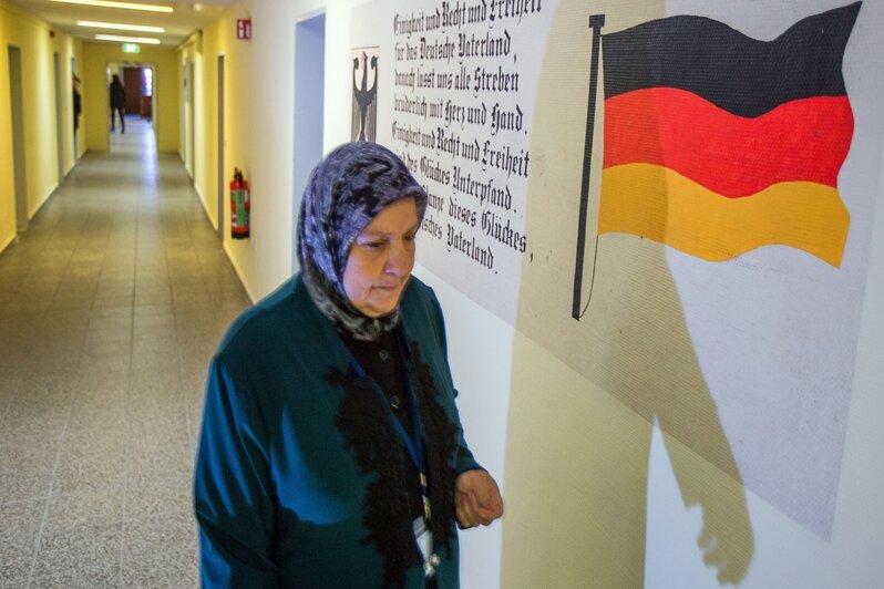 Eine Frau mit Kopftuch in der Erstaufnahmeeinrichtung für Flüchtlinge in Stern-Bucholz bei Schwerin (Mecklenburg-Vorpommern). An der Wand sind neben der Deutschlandfahne ist der Text der deutschen Nationalhymne zu sehen.