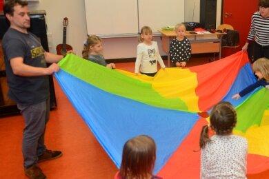 Eric Nicolai und Peggy Kikiela spielen mit den Kindern beim Theaterprojekt in Frankenberg mit einem Schwungtuch.