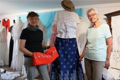 Ute Arnold (links) und Rosemarie Zimmermann, einst Meisterin im VEB Spitze - Bekleidung Pausa, haben die neue Ausstellung im Heimateck vorbereitet. Viele schöne Details sind in der Schau zu sehen.