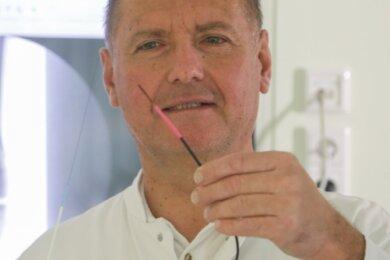 Chefarzt Dr. Rainer Fritzsche zeigt, wie durch eine neue Behandlungsmethode verstopfte Arterien mit einem Laser wieder geöffnet werden. Im Hintergrund ist ein Röntgenbild, wo man die Arterien im Knie-Bereich sieht. Am Hartmannsdorfer Krankenhaus wird die OP neu angeboten.