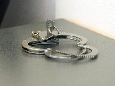Handschellen liegen auf einem Tisch.