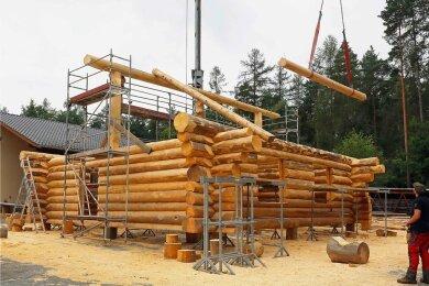 Waldarbeiter Christian Puffke bedient den Kran, der die benötigten Stämme auf das Blockhaus hebt.