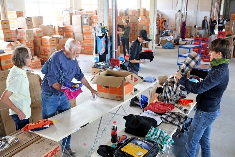 Ehrenamtliche Helfer sortieren Kleidung für Flüchtlinge in Leipzig