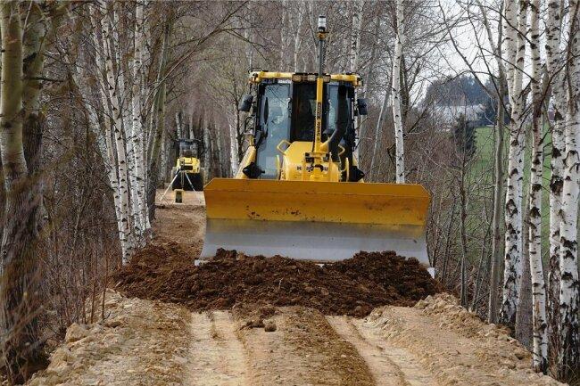 Ein Planierraupe begradigt den Damm, auf dem schon bald der neue Geh- und Radweg entstehen soll.