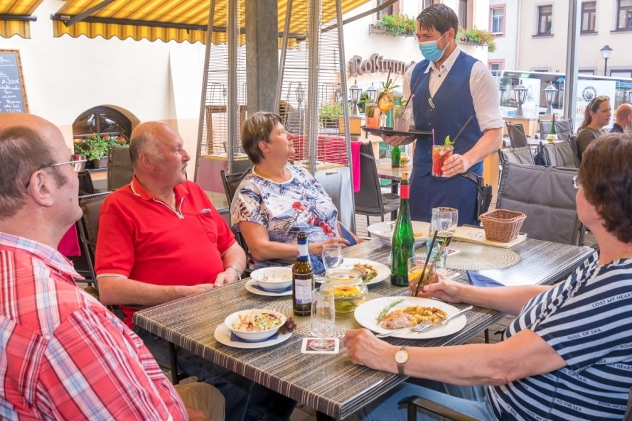 """Endlich wieder Gäste: Restaurantleiter Marcel Petke serviert auf der Terrasse vom """"Weißen Roß"""" in Marienberg den Familien Urban (vorn) und Albrecht zum Essen hausgemachte Limonaden."""