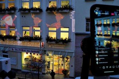 Mittels 8000-Watt-Beamer saust der Weihnachtsmann mit seinen Rentieren über die Fassade der Zwickauer Straße 9. Mit einem Smartphone wird das Ganze im Livestream auf Instagram übertragen.