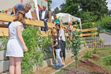 Den Mädchen und Jungen der Wohngruppe macht es viel Spaß, die Tomaten und Kräuter in den Formsteinen unterhalb der Terrasse zu ernten. Das Gießen gehört natürlich auch dazu.