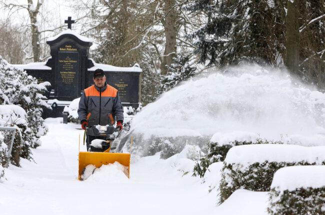 Auf dem Hohenstein-Ernstthaler Friedhof sorgt Thomas Jekel mit einer Schneefräse dafür, dass die Besucher gut zu den Gräben gelangen.