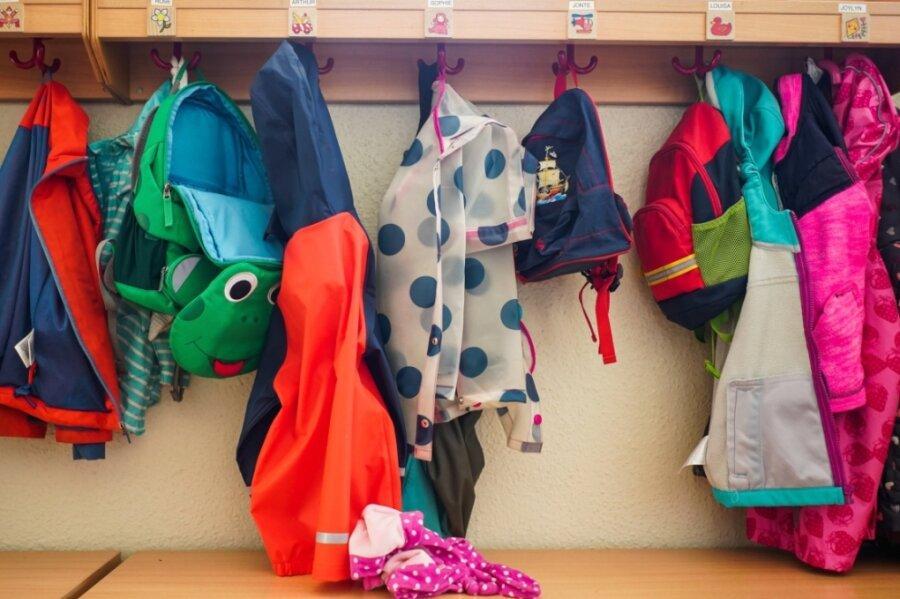 Symbolbild: Jacken und Rucksäcke hängen in der Garderobe einer Kita. Ab Dienstag dürfen berufstätige Eltern in Sachsen ihre Kinder wieder zur Kita bringen.